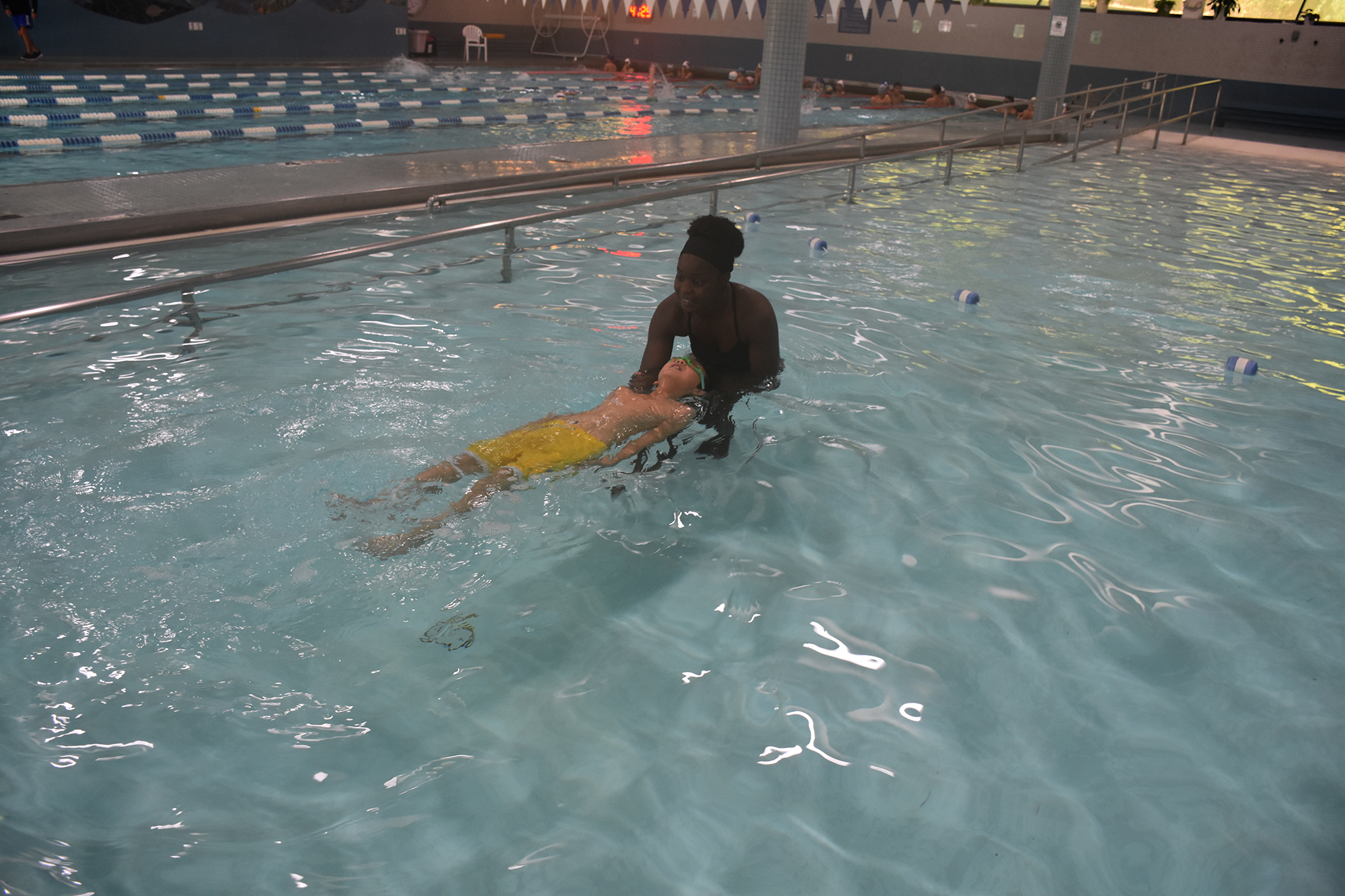 Person supporting another person as they float on their back in the pool