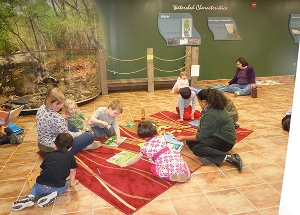 Kids sit in a circle surrounded by a Croydon Creek exhibit