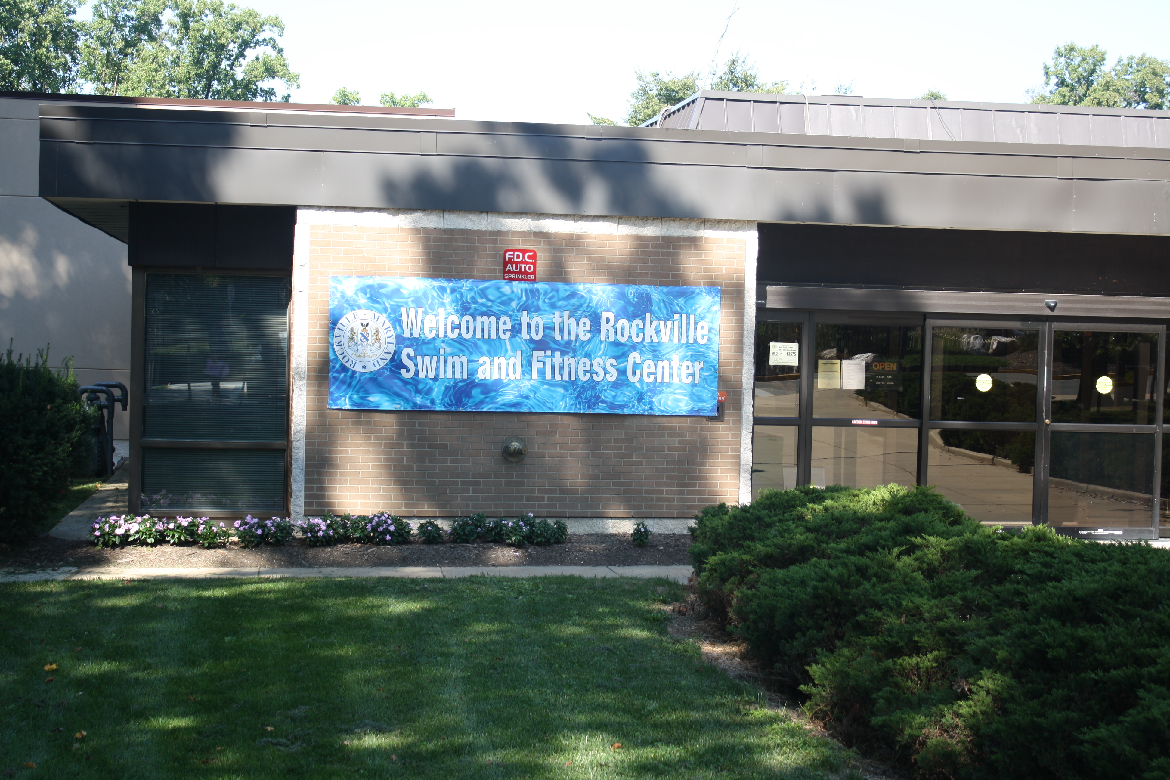 Outside of a brick building with a banner reading Rockville Swim and Fitness Center