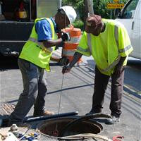 Two men fixing water main in street