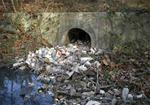 Outfall to stream filled with trash