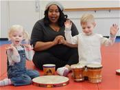 Two children with adult enjoying music class